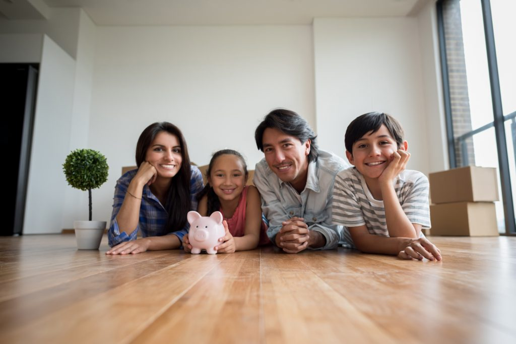 Stock photo of family with a piggybank in a new home