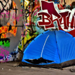 Stock photo of a tent erected in front of a graffiti-covered wall.